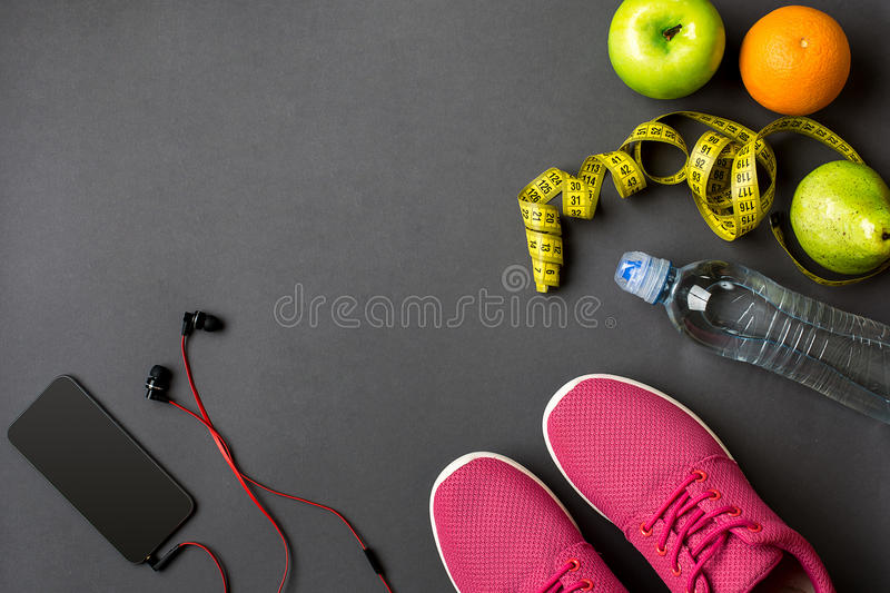 Workout plan with fitness food and equipment on gray background, top view. Workout plan with fitness food and sport equipment on gray background, top view. Copy stock photography