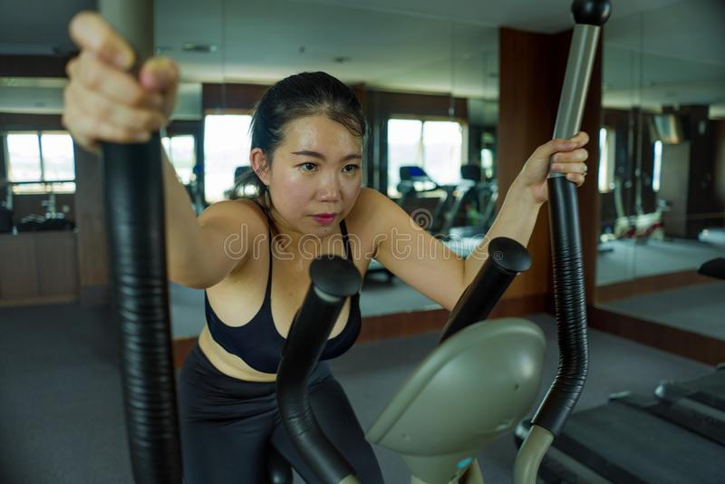 Portrait of young beautiful and attractive Asian Korean woman training at hotel gym or fitness club working hard in cardio. Workout portrait of young beautiful royalty free stock photography