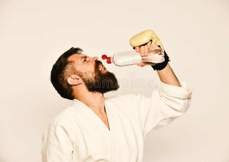 Workout and refreshment concept. Karate man with busy face. In boxing gloves holds water bottle. Combat master drinks refreshing water after training. Man with stock photography