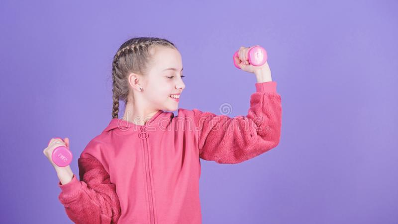 Workout of small girl hold dumbbell. Fitness diet for energy health. weight lifting for muscule. Childhood activity. Sport success. Happy child sportsman with royalty free stock image