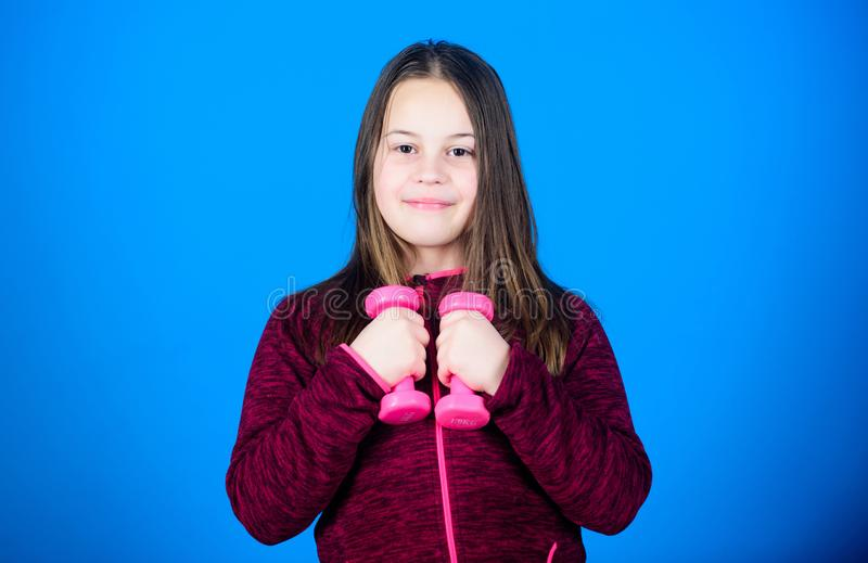 Workout of small girl hold dumbbell. Fitness diet for energy health. weight lifting for muscules. Childhood activity. Sport success. child sportsman with stock photography
