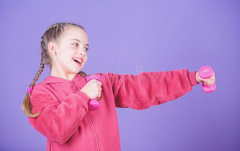 Workout of small girl hold dumbbell. Fitness diet for energy. weight lifting for muscules. happy small girl. Sport. Success. Happy child sportsman with barbell royalty free stock image