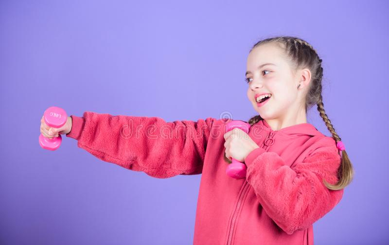 Workout of small girl hold dumbbell. Fitness diet for energy. weight lifting for muscules. happy small girl. Sport. Success. Happy child sportsman with barbell royalty free stock photo