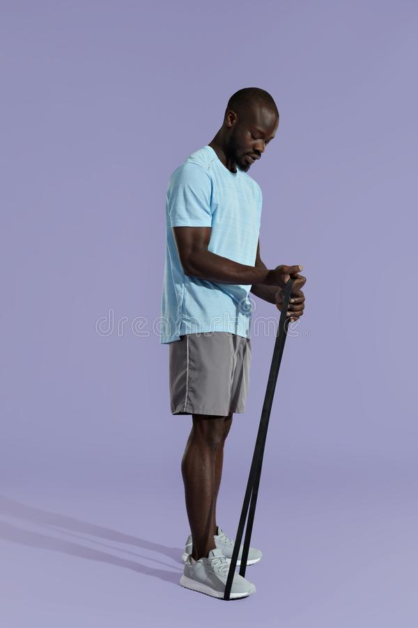 Workout. Sports man doing training band exercise on background royalty free stock image
