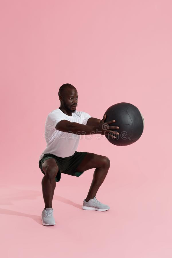 Workout. Sports man exercising, doing squats with med ball royalty free stock photo