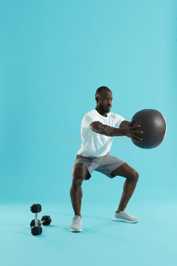 Workout. Sports man exercising, doing squats with med ball. On colorful background. Full length portrait of black fitness male model doing squat exercise stock photo