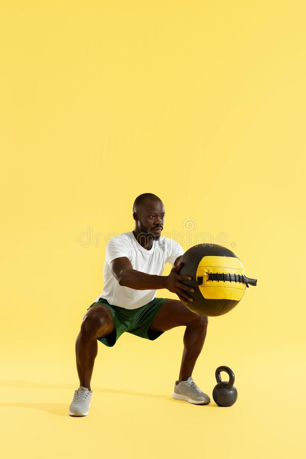 Workout. Sports man exercising, doing squats with med ball. On colorful background. Full length portrait of black fitness male model doing squat exercise royalty free stock photo