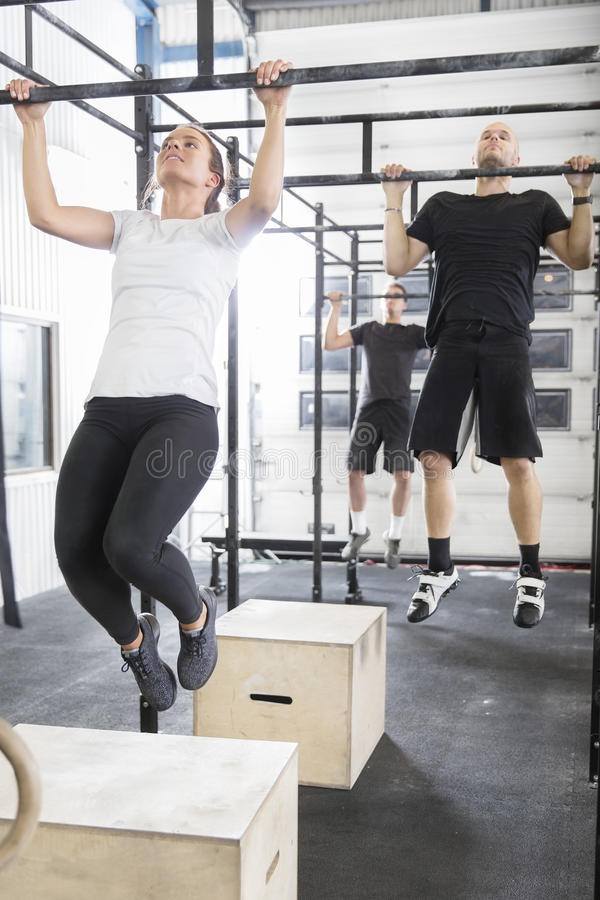 Workout team trains pullups at fitness gym stock images