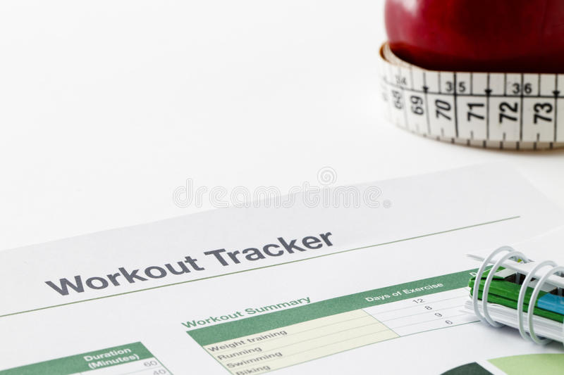 Workout tracker printout. Spreadsheet printout, spiral notebook, apple and measuring tape, copy space royalty free stock images