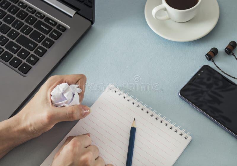workplace Женские руки с чашкой кофе наушников smartphone компьтер-книжки тетради и карандаша стоковое изображение