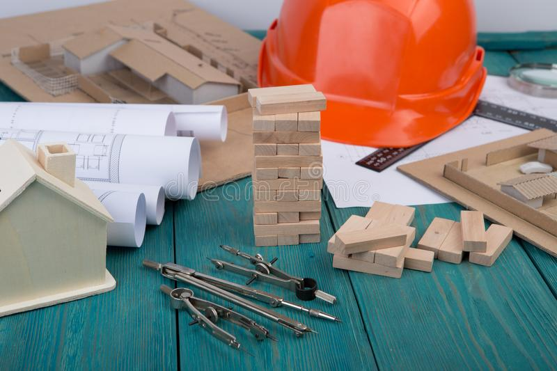 Workplace of architect - construction drawings and engineering tools, little house, model house from wooden blocks, helmet. On blue wooden background royalty free stock photos