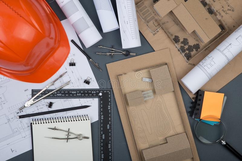 Workplace of architect - note pad, construction drawings and engineering tools, magnifying glass, helmet. On grey background royalty free stock images