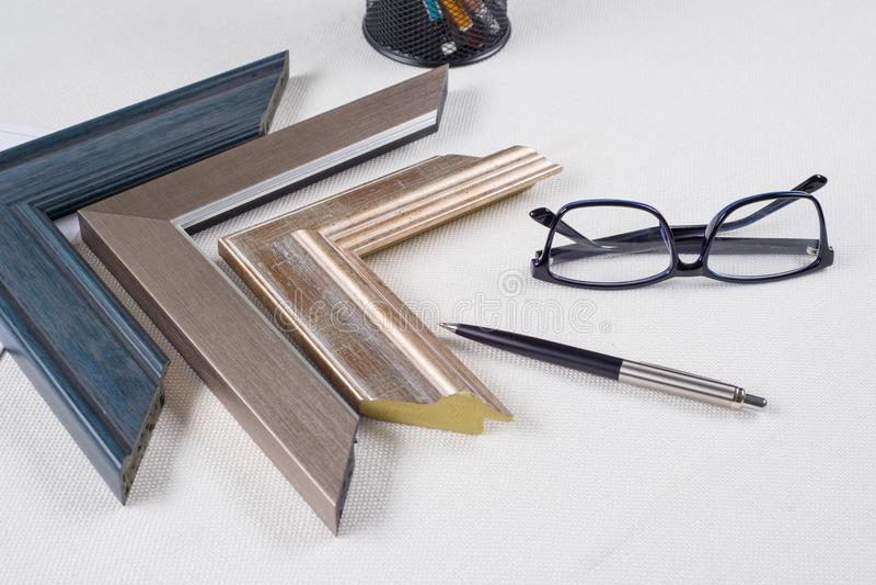 Workplace of artist, decorator, designer with samples of baguettes, frames stock image