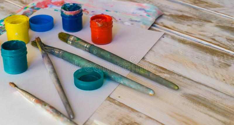 The workplace of the artist: watercolor paints, paint brushes, sheets of white paper, color palette and unfinished painting.  royalty free stock image