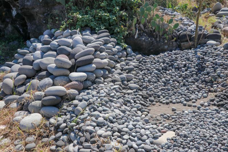 Workplace of Balinese stone gatherers. Sorted boulders by size. Natural building material. Hard work. Stones thrown from the sea a. Shore. Sea-worked boulders stock image