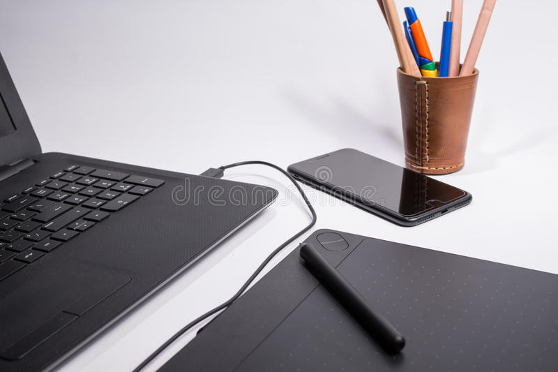 Workplace with black laptop computer, smart phone, digital graphic tablet and pen and color pens and pencils on white background stock photography