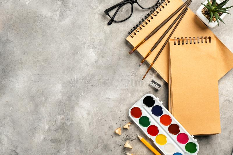 Workplace composition with paint and notebook on table, flat lay royalty free stock images