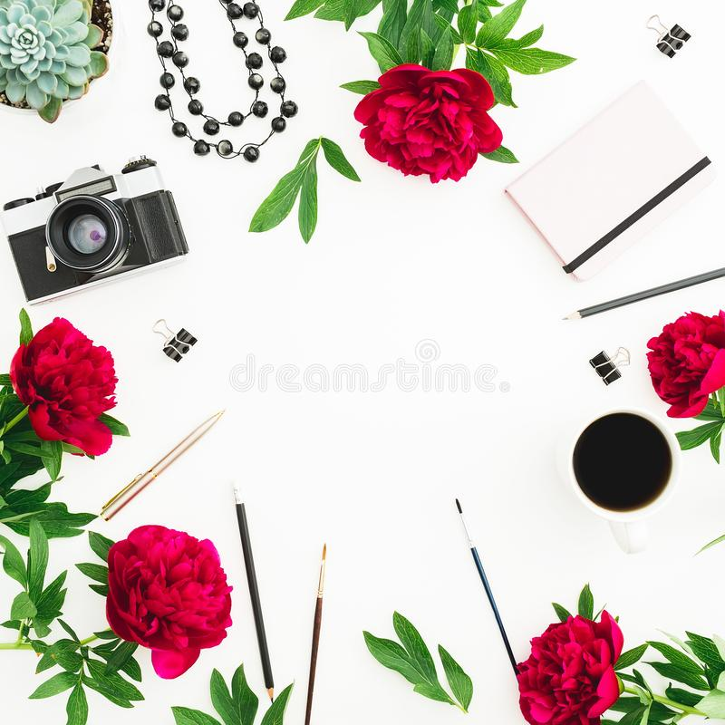 Workplace with copy space of pink dairy, red peony flowers, retro camera and accessories on white background. Flat lay, top view. royalty free stock images