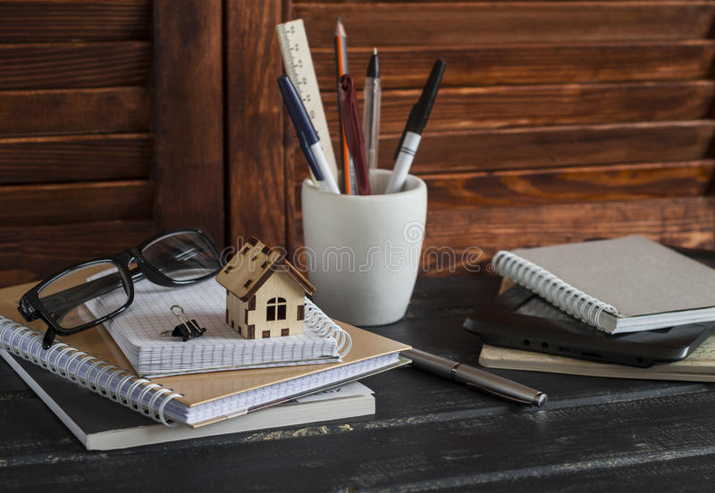 Workplace designer and architect with business objects - books, notebooks, pens, pencils, rulers, tablet, glasses and a model of a. Wooden house. Planning of royalty free stock image
