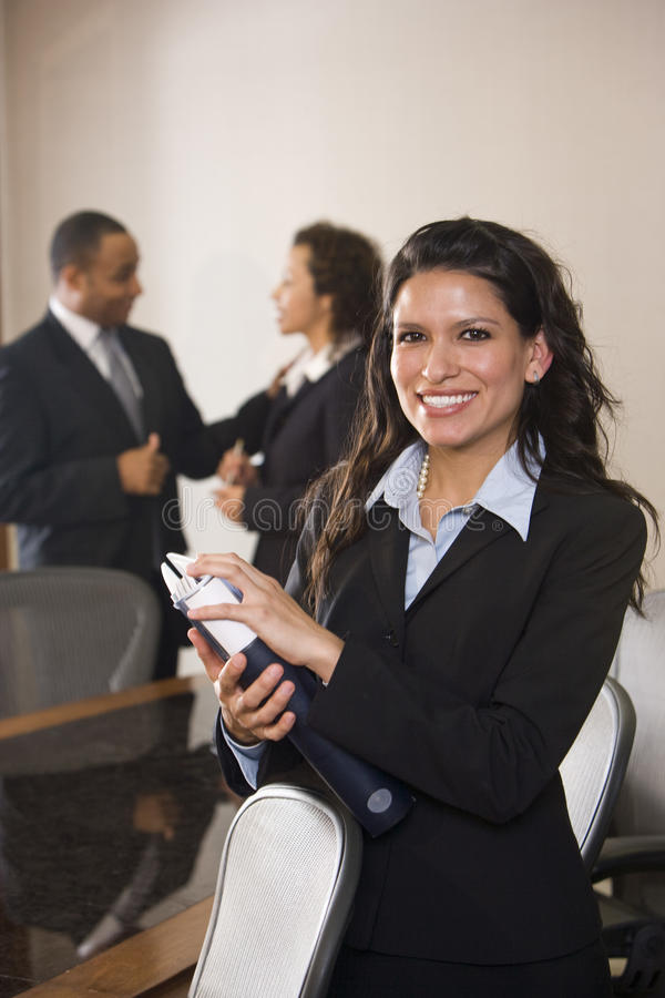 Workplace diversity. Hispanic businesswoman standing in boardroom, colleagues in background stock images