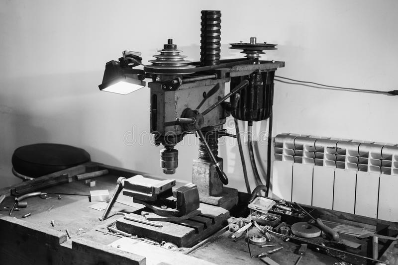 Lack and white art monochrome photography. Workplace with a drill and vice. Work at a factory. Drilling Machine stock photography