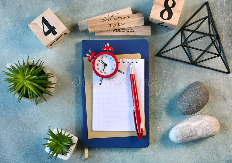 Workplace flat lay with empty notebook page, clock, flowers, stones and other scandinavian decor. Workplace flat lay with empty notebook page, clock, flowers stock images