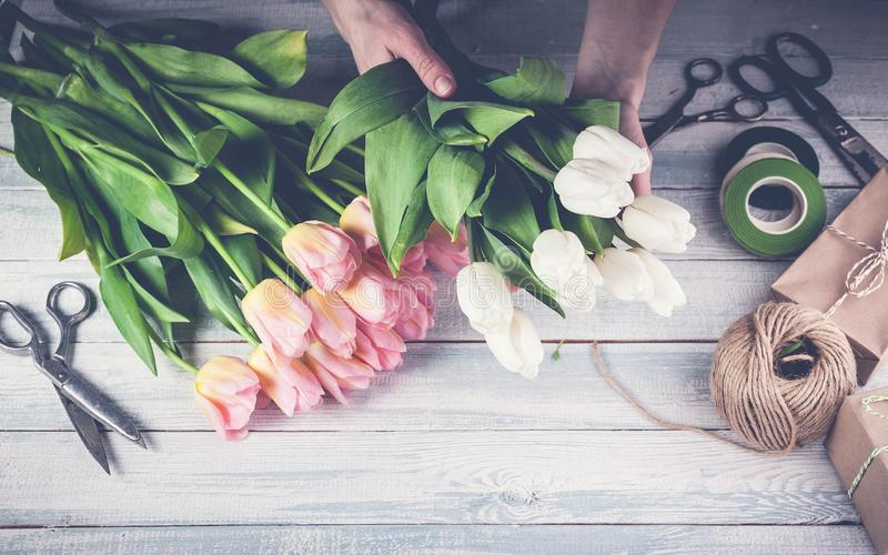 Workplace florist. Florist graceful hands holding colorful tulips. horizontal wood background. Top view. Toning stock photos