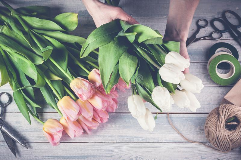 Workplace florist. Florist graceful hands holding colorful tulips. horizontal wood background. Top view. Toning royalty free stock photos