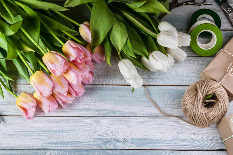 Workplace florist. Multicolored tulips on a horizontal wooden background. Top view. Multicolored tulips on a horizontal wooden background. Top view. Workplace royalty free stock photography