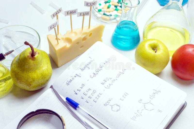 Workplace lab assistant top view. Food safety laboratory procedure, analysing fruits from the market. Notebook and blue pen on the. Lab table. In the cheese are stock photos