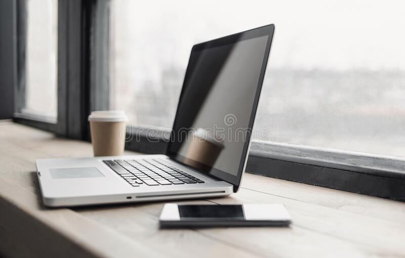 Workplace, laptop computer and mobile phone on office desk. Business, technology, place of work concept stock image