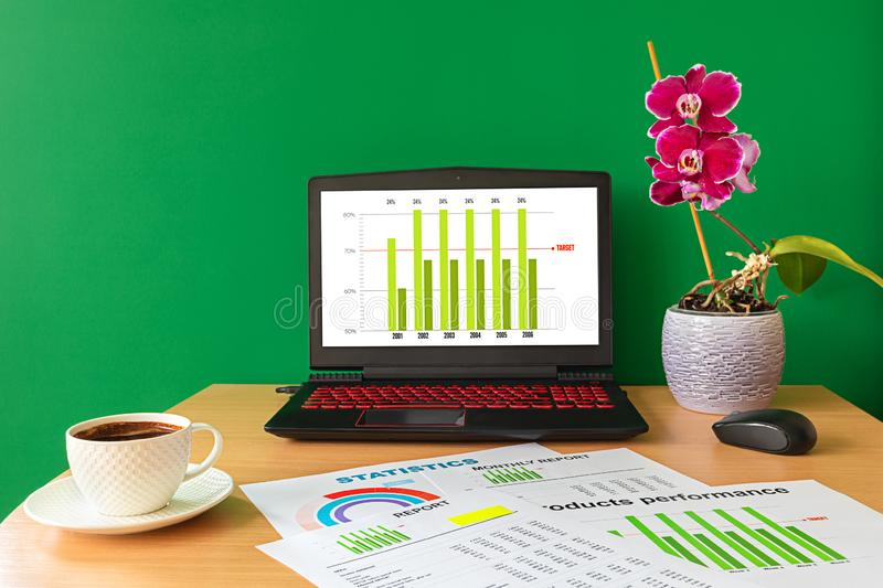 Workplace with laptop cup of coffee reports and graphs - Business graphs and charts royalty free stock photo