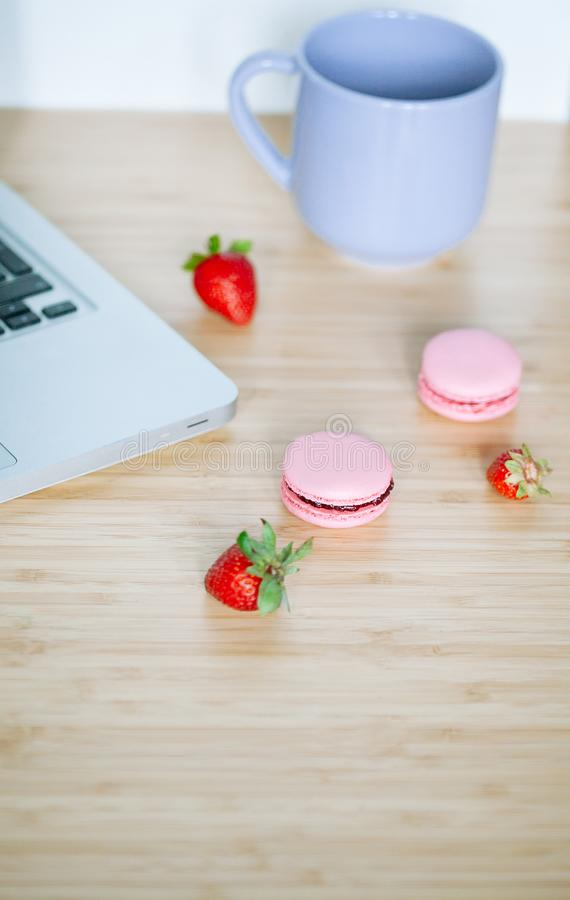 Workplace with laptop, macaroons, strawberry and cup of tea royalty free stock image
