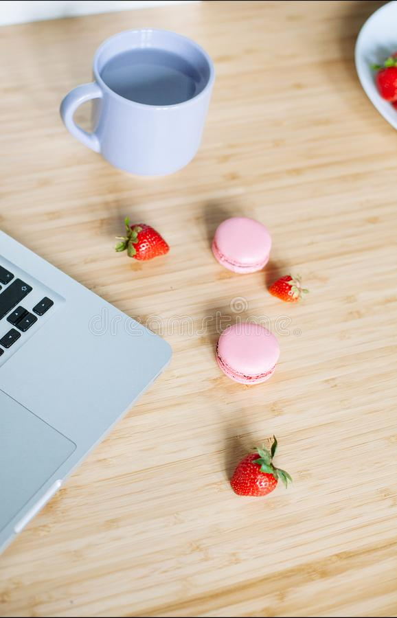 Workplace with laptop, macaroons, strawberry and cup of tea royalty free stock photo