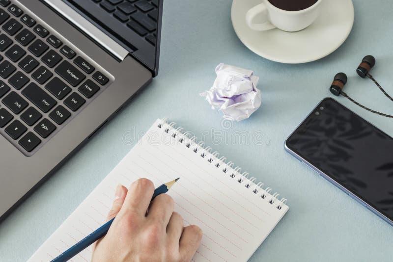 workplace Mano femminile con una tazza di caffè delle cuffie dello smartphone del computer portatile della matita e del taccuino immagini stock