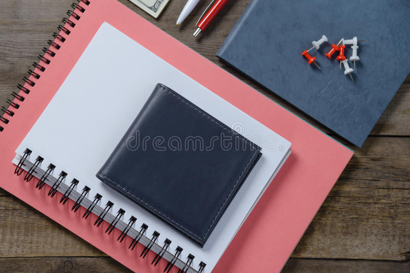 Workplace with money, stylish leather wallet, business things, pen, notebook on wooden table. Flat composition royalty free stock images