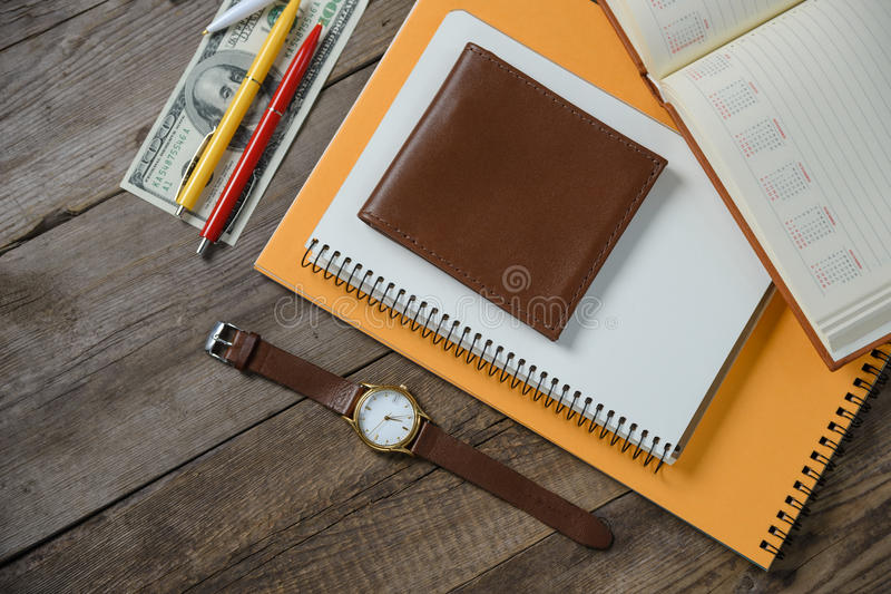 Workplace with money, stylish leather wallet, business things, pen, notebook on wooden table. Flat composition royalty free stock photography