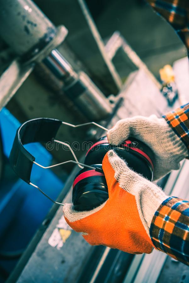 Workplace Noise Reduction. By Using Hearing Protectors. Vertical Photo royalty free stock photo