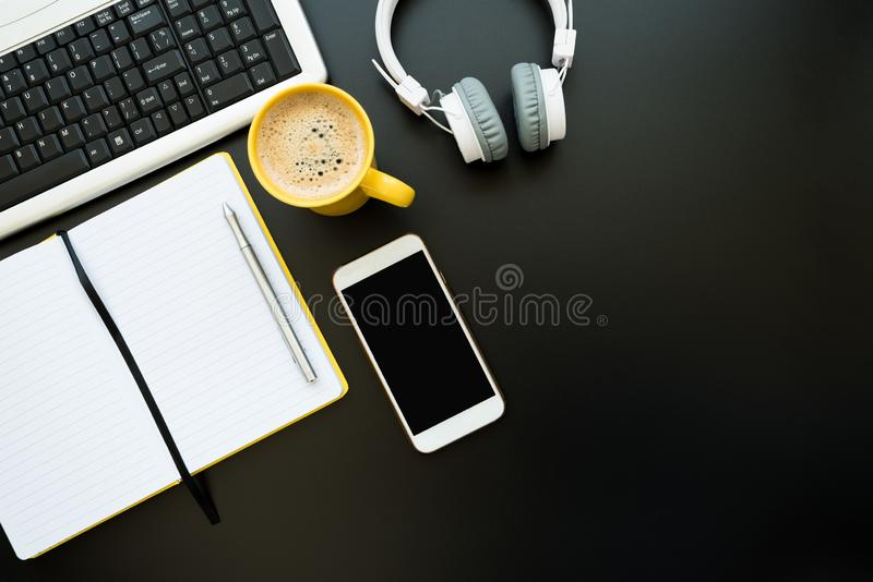 Workplace with notepad and pen, mug of coffee, smartphone, headphones and keyboard on black desk. Top view. Flat lay. Copy space stock photo