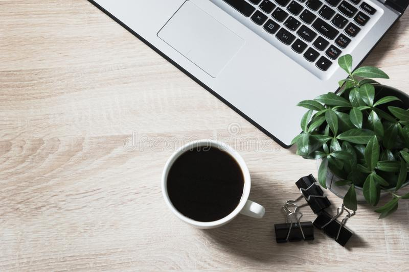Workplace with open laptop and cup of coffee on office wooden desk table. Top view, copy space. stock photo