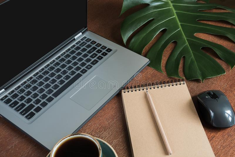 Workplace with open laptop and cup of coffee on office wooden desk table. Top view, copy space. royalty free stock photos