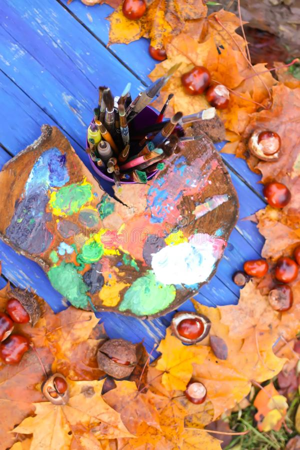 Workplace for painter in autumn park with wood palette and paintbrushes in plastic container. Fall leaves and chestnuts on wooden stock photos