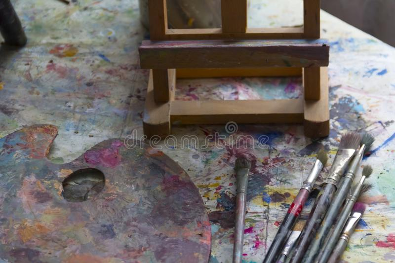 Workplace painter palette with colors and brushes. Palette of colors, creative disorder, art stock image