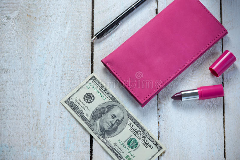 Workplace with pink leather wallet, money, pen and lipstick on white wooden table. Flat composition stock photo