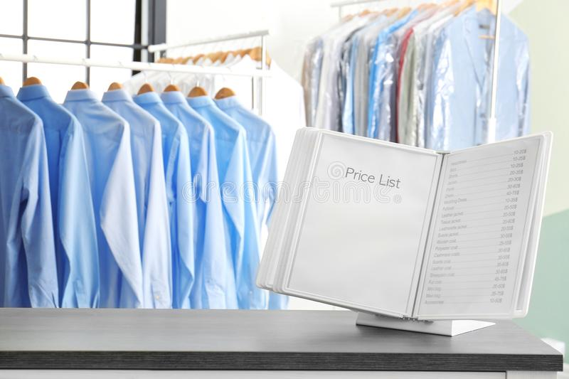 Workplace of receptionist with price list. At dry-cleaner`s stock images
