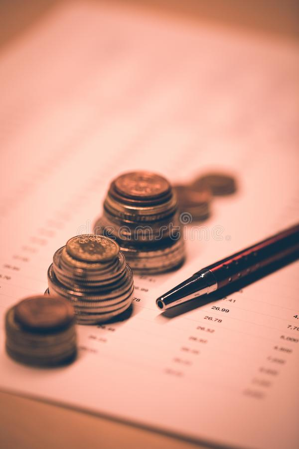 Workplace with stacked coins on business documents, charts and pen royalty free stock image