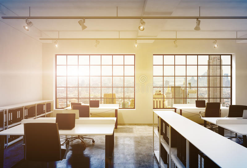 Workplaces in a bright modern loft open space office. Tables equipped with laptops; corporate documents' shelves. New York in the. Panoramic windows. 3D royalty free illustration