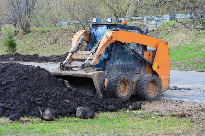 Works on the improvement of the park area. Skid steer loader royalty free stock photography
