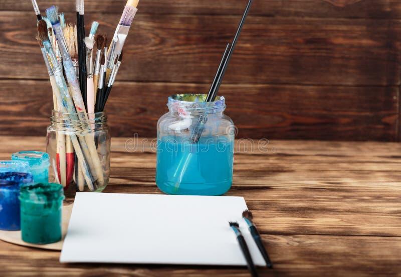 Workshop del `s dell'artista Vista superiore della tavolozza dei pennelli e delle pitture acriliche con tela bianca Insieme delle immagini stock libere da diritti