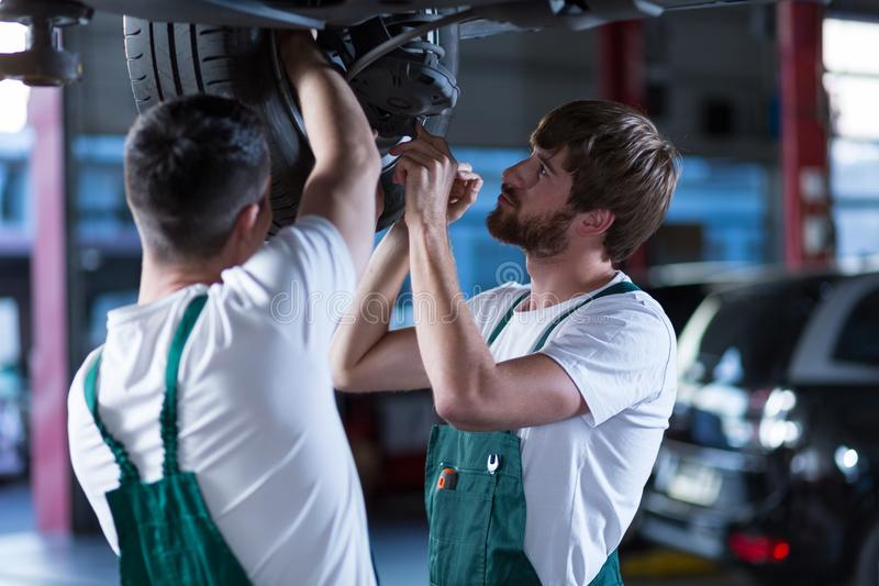 Workshop employees working together. Young workshop employees working together underneath a lifted car stock photo